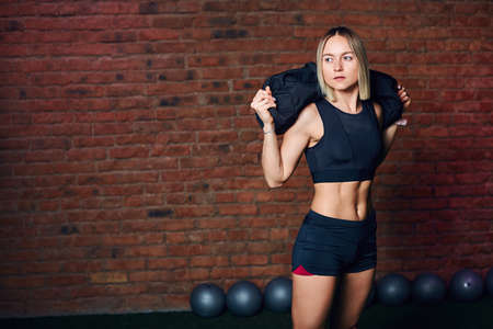 Beautiful blonde female athlete relaxing after cross-fit functional training, posing on camera with sandbag in studio with red brick walls