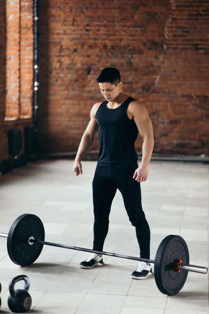strong muscular guy is standing nera the barbell and looking at it. preparation for training, concentration before workout. full length photo.