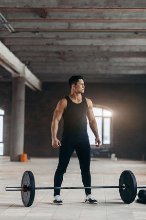 full length photo.strong man looking aside while resting near the barbell. copy space.