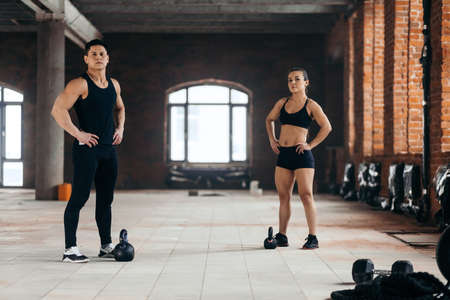 Muscular couple with hands on the hips looking at the camera during workout. full length photo. athletes resting after training. break time