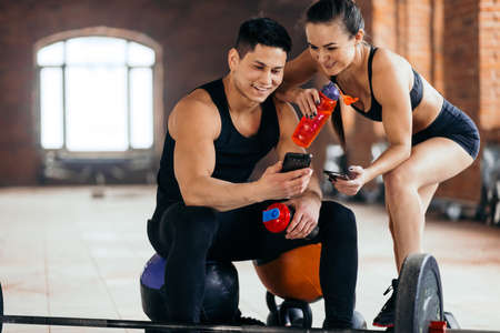 happy fit couple looking fot the Net at gym. young people brousing the net during rest in the sport club