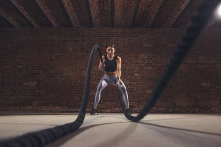 Hard work of female crossfit instructor proves that training ropes are a very dynamic workout that accelerates athletes pulse while strengthening his body, low angle panoramic shot.