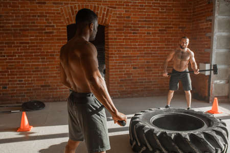 Caucasian athlete exercising with sledge hammer Hits on Tire with his personal african trainer, both shirtless men are training on tire, increasing explosive power of musculs.