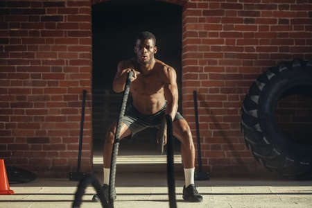 Hard work of Crossfit instructor of African ethnicity proves that training ropes are a very dynamic workout that accelerates athletes pulse while strengthening his body.