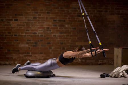 Sporty strong caucasian woman dressed in black top and silver leggins, keeps lying body on bosy while hands holding suspension straps. Exercises for a back, spin and buttock muscles.  concept
