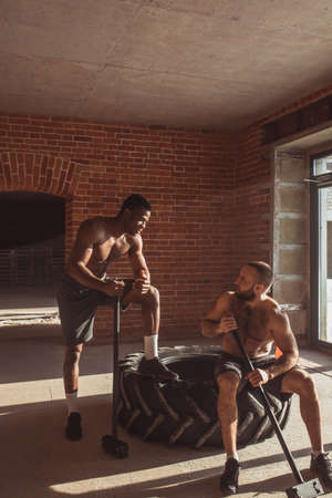 Sport, Friendship, Support and People Concept. Two interracial male friends resting after practicing Sledge hammer hits in tire, engaging in functional cross fit training.
