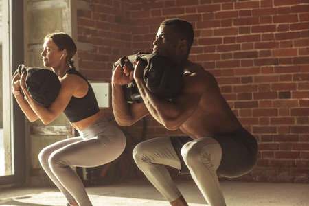 Young mixed-race fit couple doing squats exercise, with heavy sandbag in gym. A crossfit sand bag is advanced level for athletes of various sports, such as crossfit trainings and contact sports