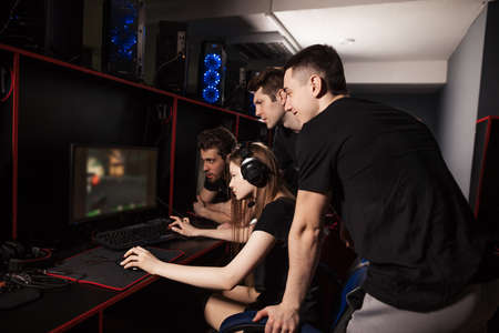 Excited pro gamer girl wearing headset, streaming online video game in PC gaming club, other players standing behind help and support her vivaciously