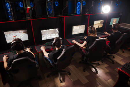 Professional Gamers participating in online cyber games tournament, sitting at pc gaming club or in internet cafe.