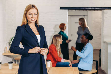 Attractive young blonde female loyer dressed in formal wear smiling at camera, ready to help her clients, colleagues working in background