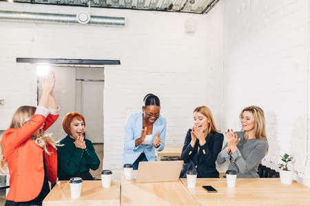 diversity, race, height, success and people concept - multi-ethnic group of happy women clapping hands and giving high five at jubilation at her success or victory.