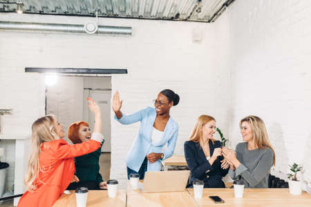 diversity, race, height, success and people concept - multi-ethnic group of happy women clapping hands and giving high five at jubilation at success or victory.