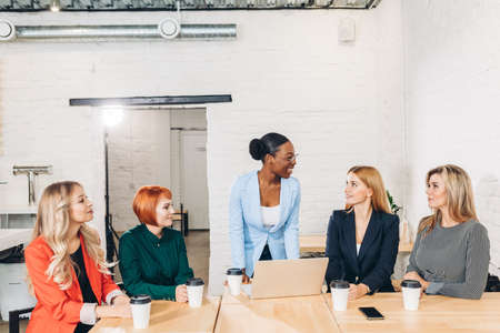 Glad cheerful businesswoman, boss of business team congratulates her co-workers in meeting room, celebrating the performance of new product