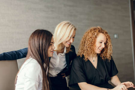 beautiful clever cute charming attractive elegant female business partners have online meeting with potential investor, gather in circle near table with laptop at office