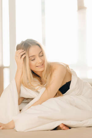 attractive positive woman in black bra closing her eyes from pleasure and anticipation lying on bed covered with white blanket.