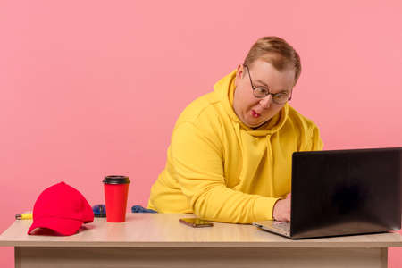 Education, work, overwork concept. Ridiculous, tired from work, mad man in yellow sports cloth look at monitor of a pc with comical foolish grimace, isolated on light pink background Standard-Bild