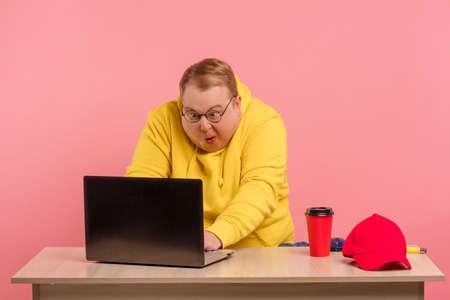 Funny plump man geek in yellow sweatshirt having foolish face expression using laptop with funny freak grimace Reklamní fotografie