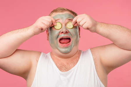 Happy funny tubby man with facial clay mask for skin care having fun with cucumber slices isolated over pink background