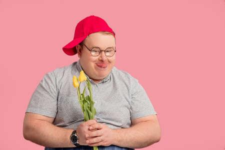 Man holding flowers on pink background. Stok Fotoğraf