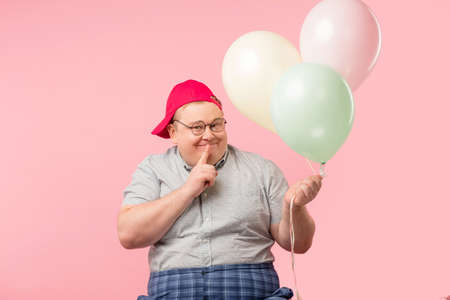 Man holding balloon with pink background.