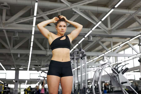 muscular fit woman holding her hair and posing in gym, beautiful bodybuilder female in sportswear looks away, going to do exercises
