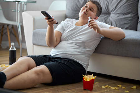 overweight fat boy eat junk food while watching tv alone at home, sit on the floor with french fries, carbonated drink, chips. enjoy unhealthy lifestyle