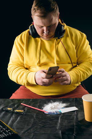 fat drug addict surfing the net. close up photo.gadget concept. lifestyle, free time , spare time. guy sending message, e-mail to a customer. distribution of drugs