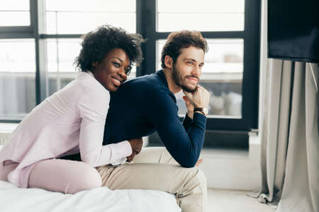 Faithful, affectionate african woman is sitting behind and hugging tenderly her handsome husband, they watching tv while sit on the bed in spacious room.