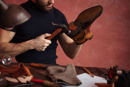 close-up cropped photo of shoemaker repairing shoes by nailing a heel, industry,small business Stock Photo