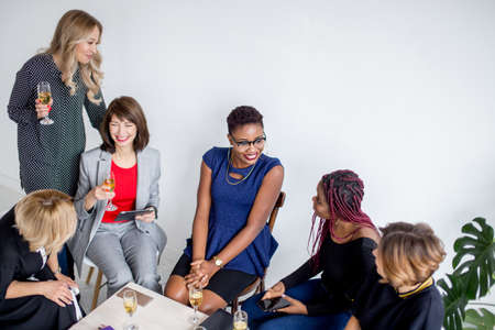 Young Women Entrepreneurs, participating in workshops, drink alcoholic beverages after a business meeting. Casually dressed females celebrate a successful project.