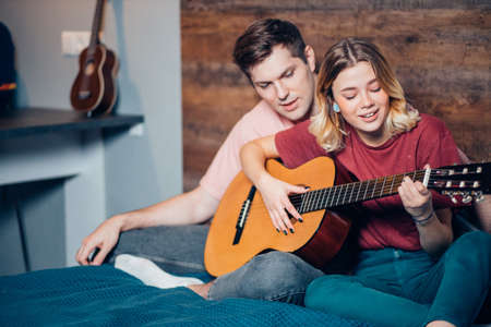 two romantic people in love sit together on bed, playing the guitar. caucasian people sit together at home