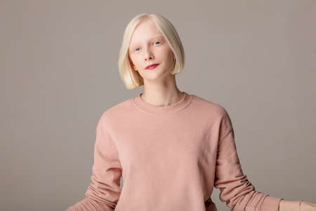 smiling attractive girl in pink stylish sweater isolated on the grey background, close up photo.