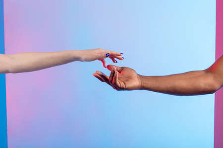 Caucasian girl and African American boy holding hands tight. close up photo. giving a hand to best friend, help concept. support, isolted blue background