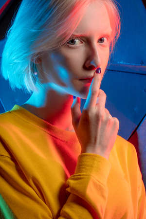 beautiful albino woman with finger on lips looking at the camera , isolated over blue background, secret, close up photo. mystery 스톡 콘텐츠 - 154137867
