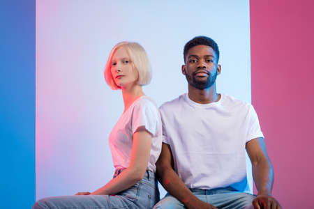 confident young diverse man and woman sitting and posing to the camera, confidence concept