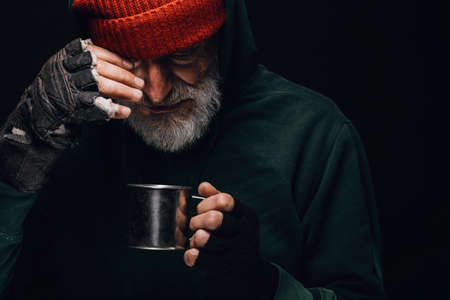 Old homeless man with grey beard covering up in green decrepit clothes holding a mug of hot tea to warm himself in a cold night