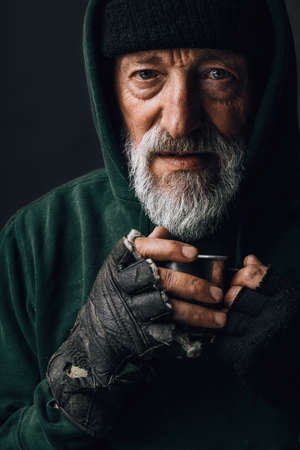 Old homeless man with grey beard covering up in green decrepit wear holding a mug of hot tea to warm himself in a cold night