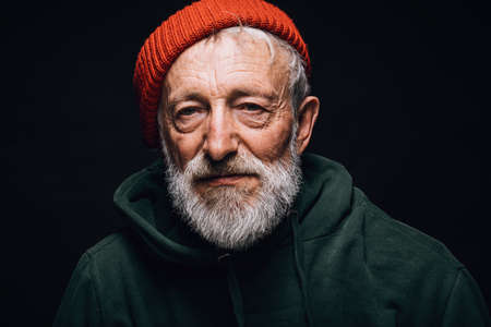 Old experienced grey-bearded man wearing red knitted hat and green warm old big-sized clothing looking at camera with serious confident expression.