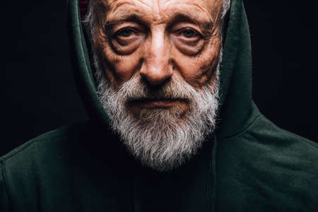 Close-up of a mature old-aged man in green hoodie with wrinkled weathered face, puffy sad eyes looking at camera with mournful expression