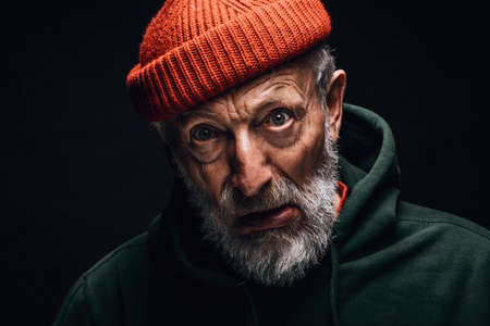 Elderly man indoor studio portrait wearing orange hat, having white beard and wrinkled weathered face, looking at camera with crazy confused expression. Mental Aging Disorders concept