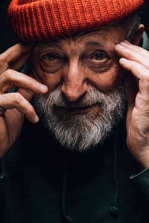 Close up portrait of bearded old man in orange hat with wrinkled weathered face stares hopefully at camera holding hands near the temples, isolated over black background. Human emotions concept.