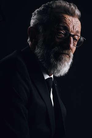 Portrait of handsome elderly well-groomed CEO posing in black formal suit on dark background