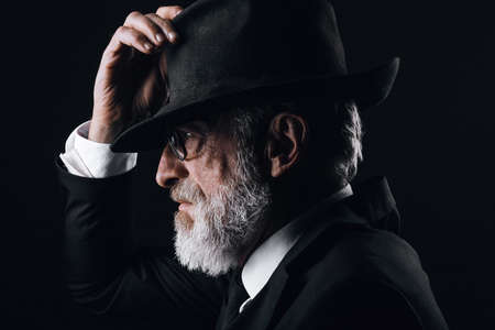 An old male actor playing an English spy role, dressed in black suit, hiding behind fedora hat, having mysterious elegant look. Isolated studio portrait over dark background
