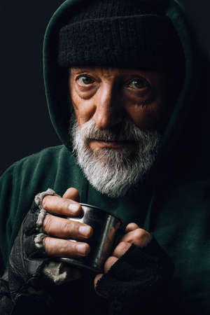 Elderly beggar being frozen outside, drinking hot water to get warm, looking at camera isolated over black studio background. Old age, Homeless concept. 스톡 콘텐츠 - 154144348