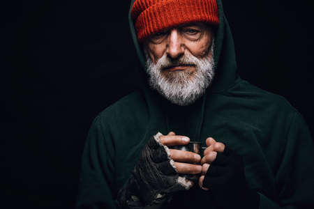 Elderly beggar being frozen outside, drinking hot water to get warm, looking at camera isolated over black studio background. Old age, Homeless concept.