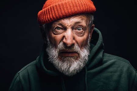 Portrait of old weird bum in orange hat with crazy eyes and puzzled confused expression on black studio background
