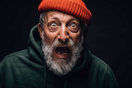 Frightened shocked bearded elderly man stares at camera with open mouth and bugged out eyes, bated breath, seen smth he was scared of, isolated over black background. People, faces, emotions concept