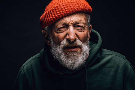 Old homeless man dressed in worn but clean outdoor clothes and hat looking at camera with screwed up eyes and interrogative expression having sight or hearing problems.