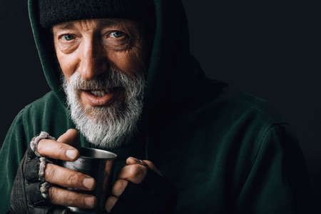 Frozen homeless bearded old man with grey hair and wrinkled face, looks at camera with grateful expression and holds a steel mug with coins given as alms, posing at studio over black background