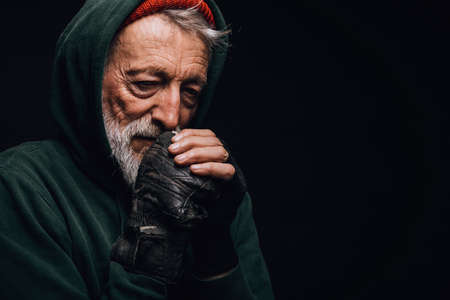 Face portrait of gloomy experienced grey-haired old-aged man with skin lined with wrinkles, dressed in warm shabby clothing as a tramp, rubbing his cold hands with hopeless humble expression.